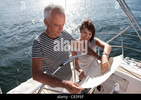 Vieux couple reading map on voilier Banque D'Images