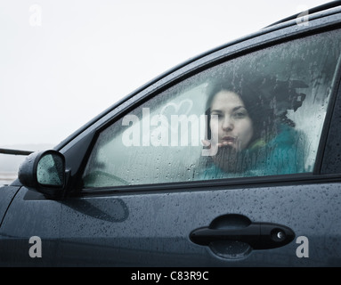 Teenage girl blowing kiss from car Banque D'Images