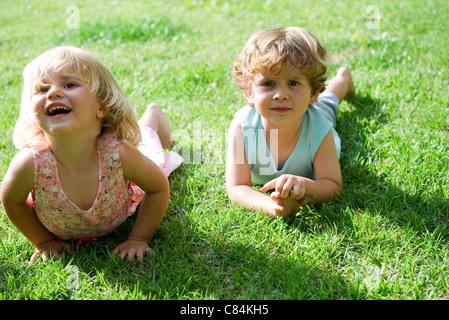 Les jeunes frère et sœur lying on grass Banque D'Images