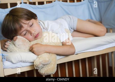Le garçon endormi dans un lit bébé Banque D'Images