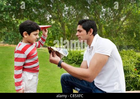 Père et fils s'amusant avec des avions en papier Banque D'Images