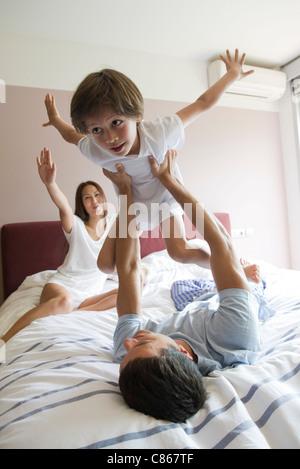 Famille ensemble sur lit, père fils de levage dans l'air Banque D'Images