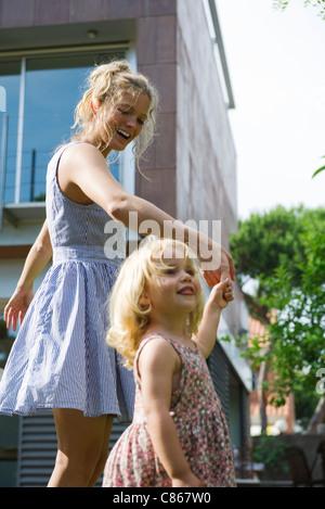 Mère et fille marcher main dans la main à l'extérieur Banque D'Images