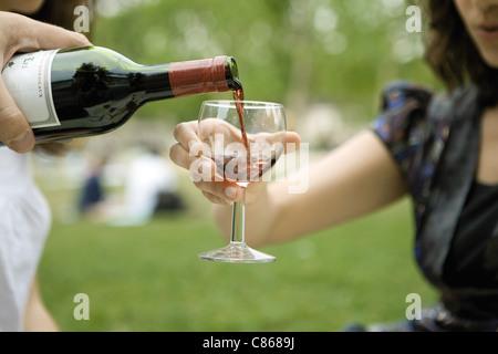 Verser un verre de vin rouge à l'extérieur Banque D'Images