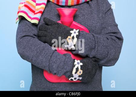 Photo d'une femme tenant une bouteille d'eau chaude rouge sur sa poitrine tout en portant des gants de laine main Banque D'Images