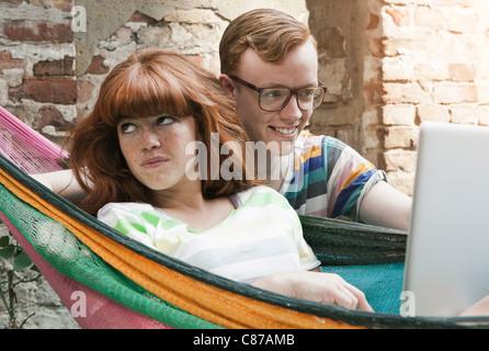 Allemagne, Berlin, young woman using laptop in hamac avec jeune homme à côté d'elle Banque D'Images