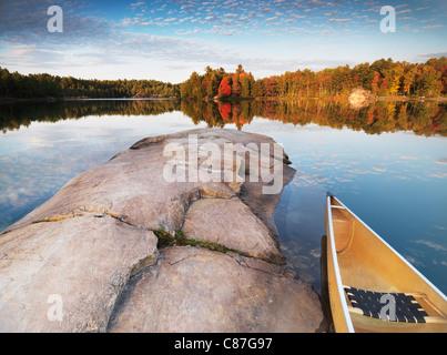 Canot à un rivage rocheux du lac George. Magnifique coucher de soleil automne nature paysage. Le Parc provincial Banque D'Images