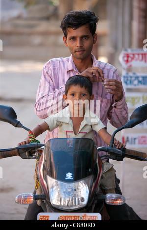 L'homme indien avec l'enfant sur une moto à Narlai village de Rajasthan, Inde du Nord Banque D'Images