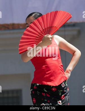 Danseuse de Flamenco se cacher derrière un ventilateur rouge Banque D'Images