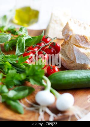 Oignons de printemps,concombre,tomates cerises,des herbes fraîches, pain et fromage Banque D'Images