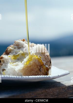 Verser l'huile d'olive sur un morceau de pain Banque D'Images