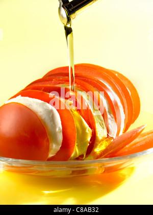 Verser l'huile d'olive sur un plat de tomates et mozzarella Banque D'Images
