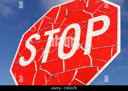 Et un panneau d'arrêt porté contre le ciel bleu. Banque D'Images