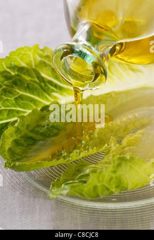 Verser l'huile d'olive sur les feuilles de laitue Banque D'Images