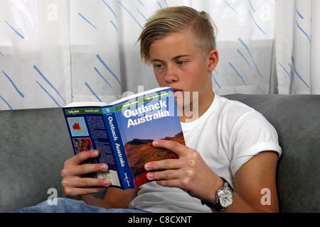 Ambiance détendue, homme, adolescent danois lecture Lonely Planet Australie Outback en préparation d'une maison Banque D'Images