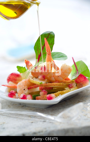 Verser une goutte d'huile d'olive sur la salade de crevettes et de poires Banque D'Images