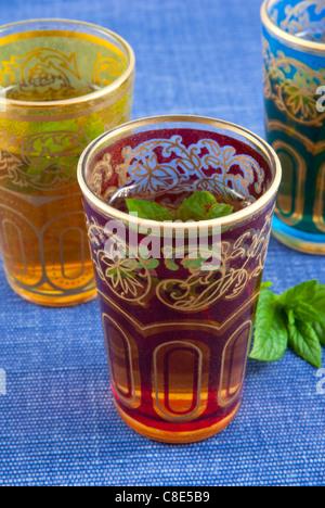 Petits verres colorés de thé à la menthe sur fond bleu . Banque D'Images