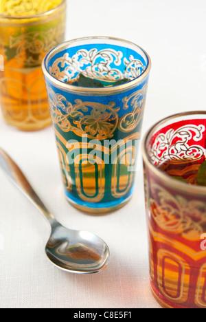 Petits verres colorés de thé à la menthe sur un fond blanc. Banque D'Images