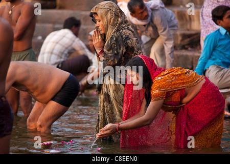 Indian Hindu pilgrim echelle et prier dans le Gange à Ghat Dashashwamedh dans la ville sainte de Varanasi, Inde Banque D'Images