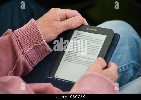Man reading book sur Amazon Kindle ebook reader Banque D'Images