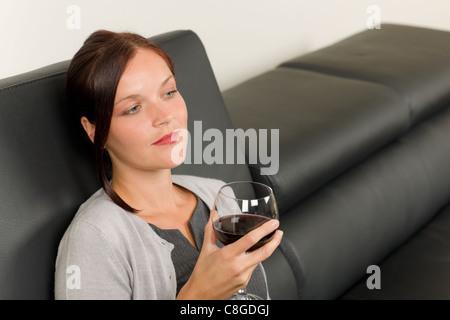 Elegant businesswoman sitting on sofa en cuir Banque D'Images