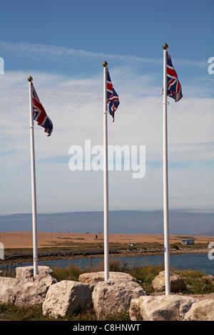 Trois drapeaux Union Jack sur des poteaux près de plage de Chesil, Portland, Weymouth en Août Banque D'Images