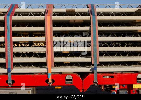 Une pile de béton préfabriqué avec poutres treillis intégré est livré à un chantier de construction. Banque D'Images