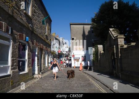 St Ives Cornwall England UK Woman walking trois chiens en laisse le long de place du marché dans cette station balnéaire Banque D'Images