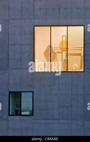 Vue sur la grande fenêtre de Hepworth Gallery, lumières allumées (lueur dorée) et pièces sculpturales exposées à l'intérieur - Wakefield, West Yorkshire, Angleterre, Royaume-Uni.