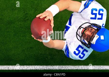 Photo prise à la verticale d'un joueur de football américain receveur attraper la balle en l'air. Banque D'Images