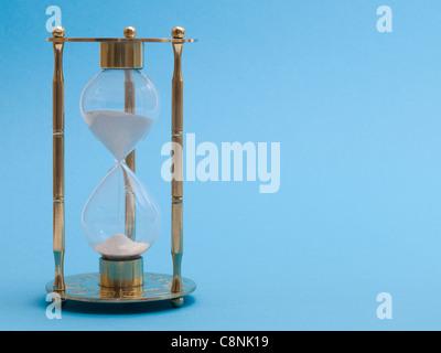 Photo détail d'un verre de sable doré devant un fond bleu Banque D'Images