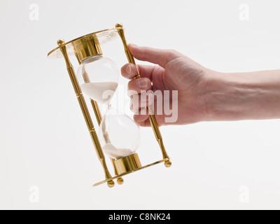 Un verre de sable doré dans une main Banque D'Images