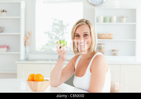 Young blonde woman holding a green apple smiling dans l'appareil photo Banque D'Images
