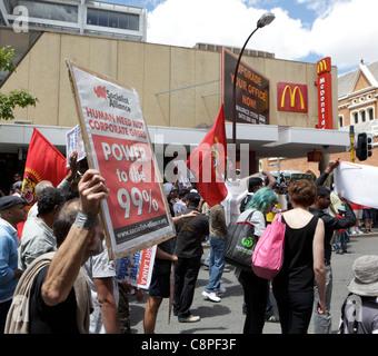 """Manifestant est titulaire d'un """"Pas besoin de la cupidité de l' étendard près d'un Macdonald's signe. Banque D'Images"""