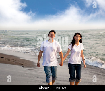 Heureux couple d'âge moyen marche sur la plage Banque D'Images