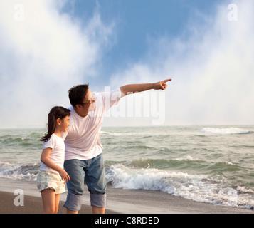 Père pointant et petite fille à elle sur la plage Banque D'Images