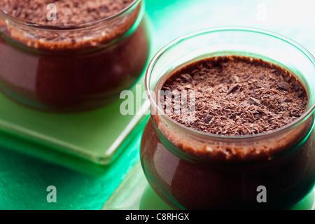Photographie du gros deux pots de mousse au chocolat sur fond vert Banque D'Images