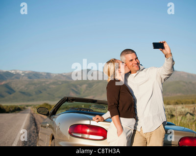 USA, Utah, Kanosh, Mid adult couple photographing themselves en face de montagnes majestueuses Banque D'Images