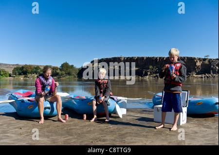 Mère et enfants faites une pause au cours d'un voyage de rafting sur la rivière Oranje à Noordoewer Namibie Banque D'Images