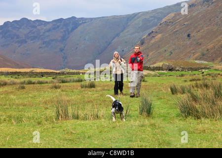 Deux personnes qui prennent un chien tirant sur une longue vallée dans Langstrath dans Parc National de Lake District Banque D'Images