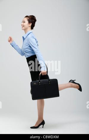 Asian Businesswoman Holding en hâte, valise à la main