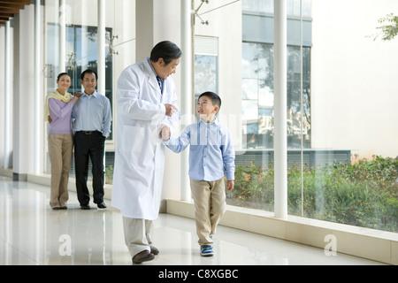 Jeune famille promenades dans un couloir de l'hôpital avec un médecin Banque D'Images