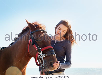 Girl petting horse on beach Banque D'Images