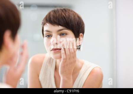 Woman applying moisturizer in mirror Banque D'Images
