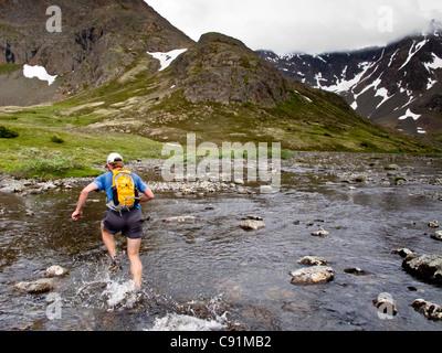 Trail Runner éclabousse par Middle Fork Creek Campbell lors de l'exécution de Mont Elliot à Wolverine Peak de Rusty Banque D'Images