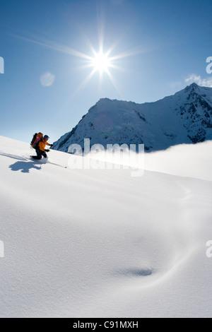 La skieuse de l'arrière-pays redescend par poudre et soleil pour la selle entre pic du cratère et le Mont Spurr, Banque D'Images