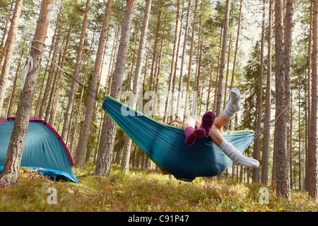 Women relaxing in hammock at campsite Banque D'Images
