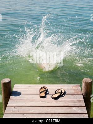 Tongs sur terrasse en bois au bord du lac Banque D'Images
