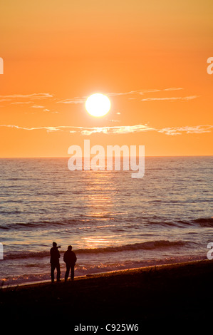 Un couple marche le Homer Spit plage au coucher du soleil le long de la baie Kachemak, péninsule de Kenai, Southcentral Banque D'Images