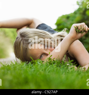 Girl laying on grass en chemin de terre Banque D'Images